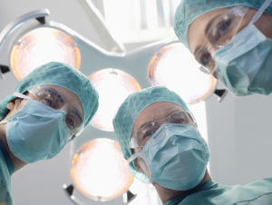 surgeons looking down at patient from patient's perspective